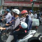 Armador av skotrar och motorcyklar präglar många storstäder. Baby matas med nappflaska under färd i Saigon, Vietnam.
