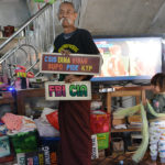 "Lu Maw, en av de berömda ""Mustaschbröderna"" (The Moustache Brothers) i Mandalay, Burma, visar skyltar ur sin satirrepertoar."